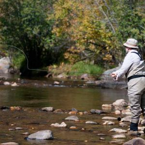 man standing on rocky river bank casting his fly rod