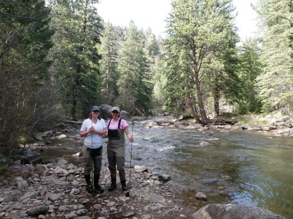 two women standing beside a river with their fly fishing rods
