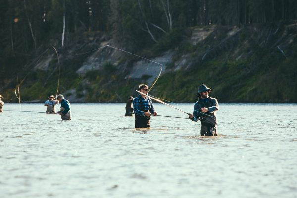 group of men standing in a river fly fishing