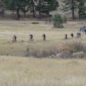 group of mountain bikers riding a flat filed trail