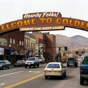 sign arching over a road that reads howdy folks welcome to golden where the west lives