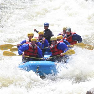 a boat of rafters navigating rocks and rapids