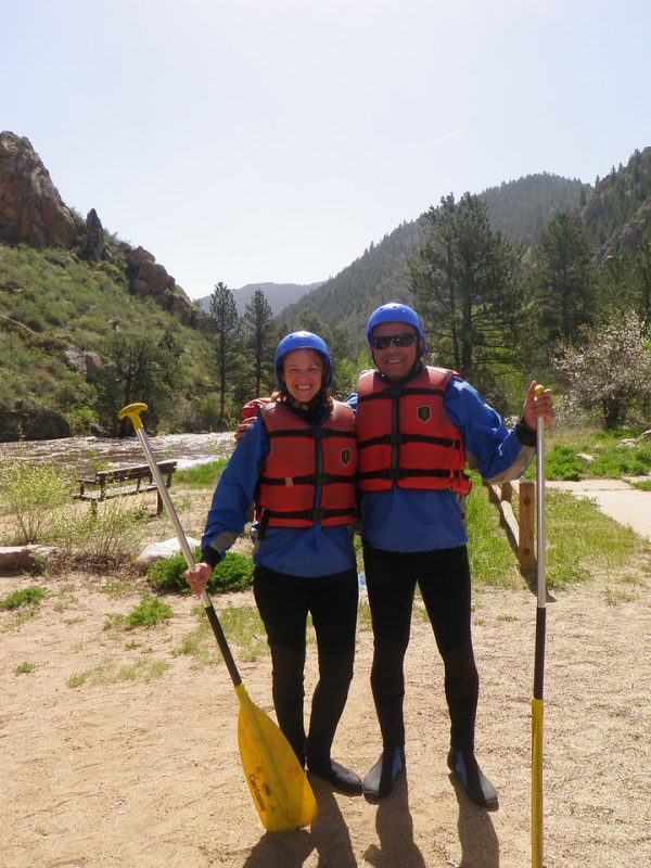 two rafters posing in their PFDs with paddles