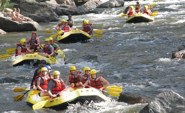 three yellow raft boats floating down calm rapids