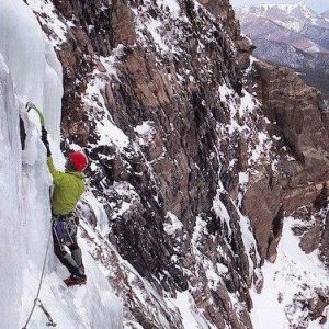man ice climbing with axes