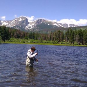 young man wading in deep water to fly fish