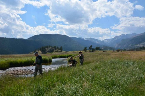 three people looking for a good spot to fish in a mountain meadow