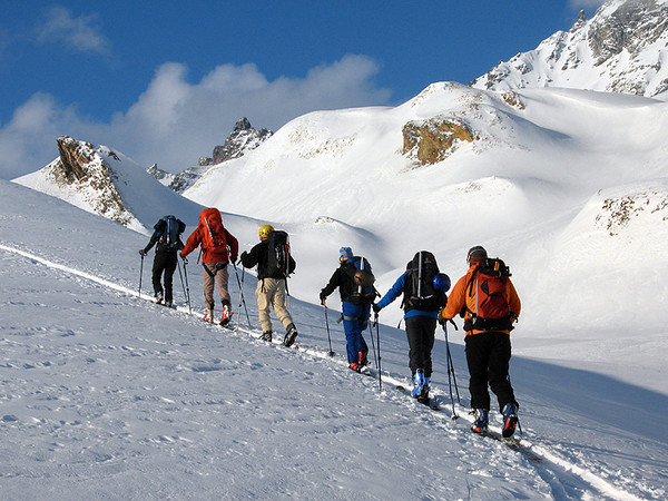 ski touring group climbing up a snowy mountain hill