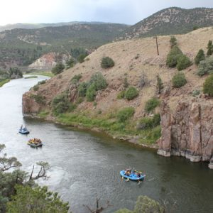 aerial shot of raft boats floating on calm water in a canyon