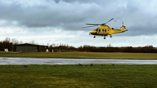 yellow helicopter about to land at a small airport field
