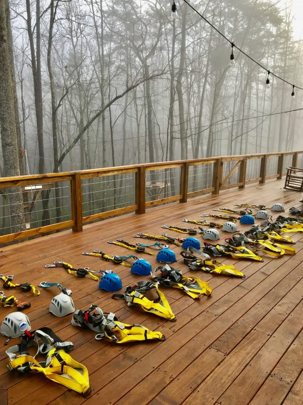 zip lining gear staged for a group helmets and harnesses