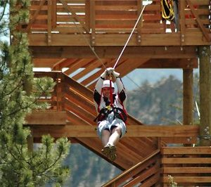 man zip lining away from a tower
