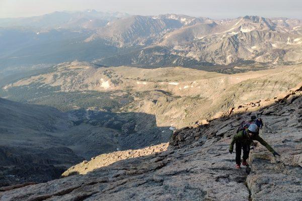 group of people hiking up steep mountain terrain
