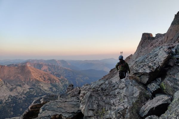 man hiking on top of rocky mountains with a pack and poles