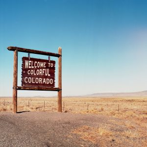 wooden sign that says welcome to colorful Colorado against blue sky