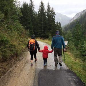 mom and dad holding childs hands walking down a path with evergreens and mountains