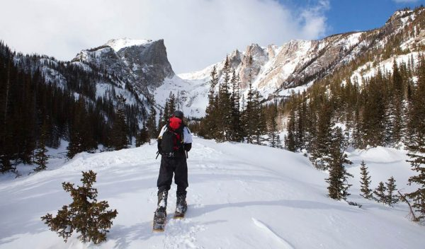 guy snowshoeing in rocky mountians